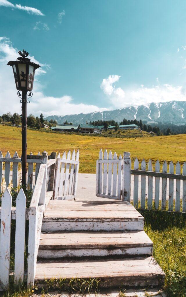 black lamp post beside white wooden fence during daytime